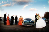 photo of a bridal party in front of two cars